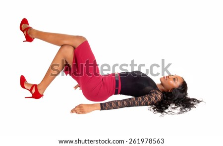A slim tall young African American woman lying on the floor in a red skirt