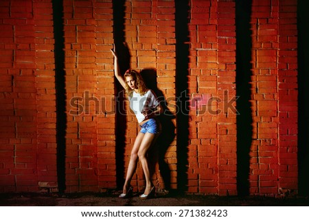 A slim young attractive girl is posing at a red brick wall background at a night city street. - stock photo