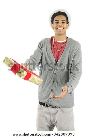 A slim young man happily offering the viewer a Christmas gift, the ring of fluff from his Santa hat seen around his hair.  On a white background. - stock photo