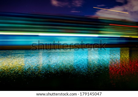 A slow shutter shot of a container ship passing by Savannah, Georgia late in the evening. - stock photo