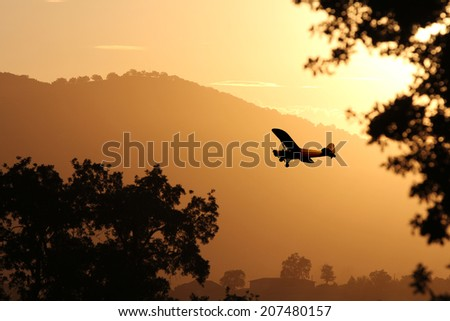 A small airplane flying through the golden yellow mountains preparing to land at sunset. - stock photo
