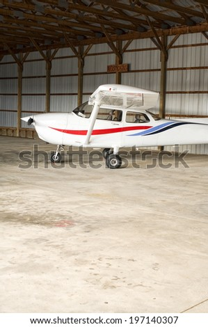 A small airplane in a no smoking hangar. - stock photo