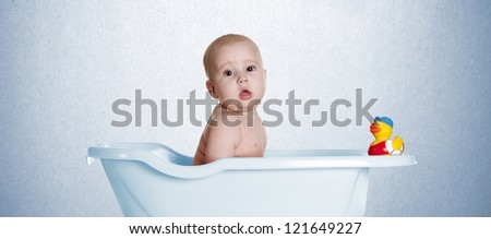 a small baby, playing in a bath with her duckling - stock photo