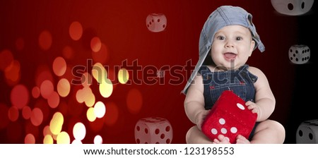 a small baby with his cap and a dice - stock photo