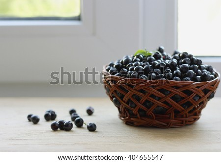 A small basket of ripe juicy fresh blueberries amid the brightly lit Windows. - stock photo