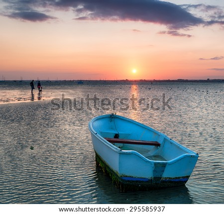 A small blue boat on the beach at Sandbanks in Poole, Dorset - stock photo