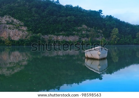 a small boat floating in a lagoon - stock photo