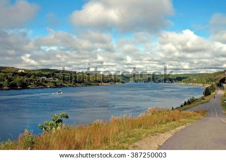 A small boat makes its way along the Cape Cod Canal in Massachusetts - stock photo