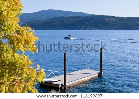 A small boat on a blue lake during early fall with changing trees by a floating dock and mountains in the distance. - stock photo