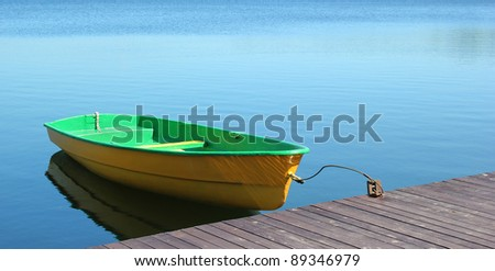 A small boat parking at a wood dock - stock photo