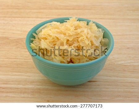 A small bowl filled with canned sauerkraut on a wood table top. - stock photo