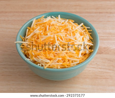 A small bowl filled with shredded white cheddar, sharp cheddar and mild cheddar cheeses atop a wood table top. - stock photo