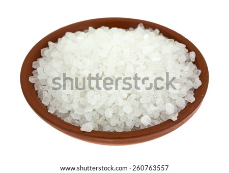 A small bowl of coarse sea salt granules on a white background. - stock photo