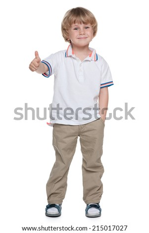 A small boy holds his thumb up on the white background - stock photo