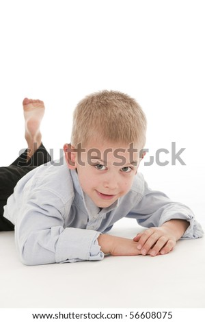 A small boy in the studio, dressed up in a suit and pretending to be a businessman, lying down. - stock photo
