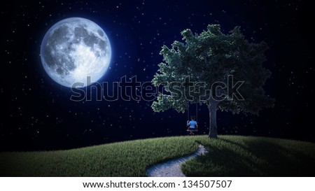 A small boy on a swing looking at the Moon - stock photo