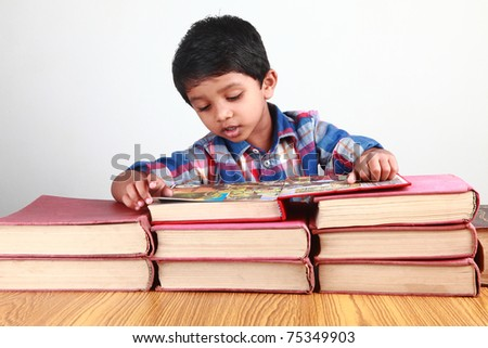 A small boy reading a book - stock photo
