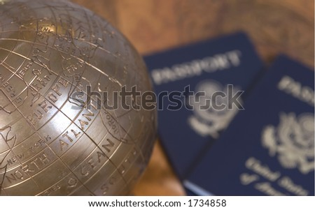 A small brass globe of the world with two passports in the background - stock photo