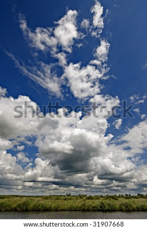a small canal with huge cloads above it - stock photo
