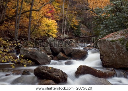 A small cascade in the beautiful autumn forests of Virginia. Taken with a slow shutter speed to smooth the water. Lots of interesting details in the water as it tumbles  its way down stream. - stock photo