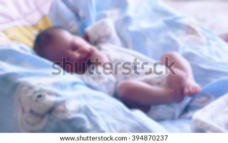 A small child lies sleeping in bed (blurred background)   The little baby is asleep in the crib at home (blurred background) - stock photo