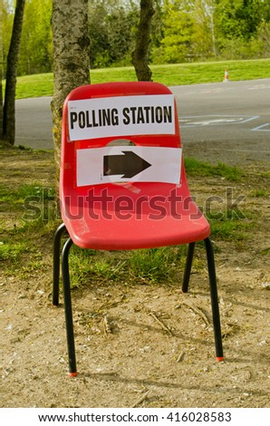 A small child's stacker chair with a sign pointing towards a polling station at a primary school on election day in Basingstoke, Hampshire, UK. - stock photo