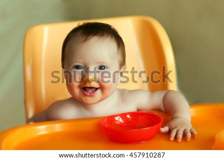 A small child sits in the chair, smiling laughing, learning to eat, play, indoor , child, dirty mashed food - stock photo