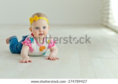 A small child sitting on the floor - stock photo