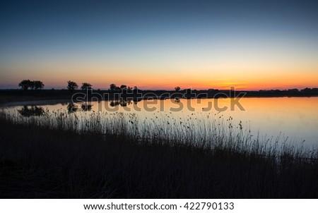 a small circular lake before dawn, still very cold morning - stock photo
