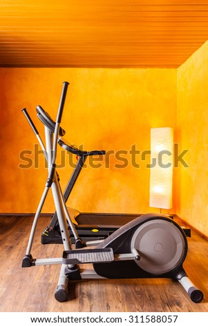 a small comfy home gym with a tread mill and an ellyptical machine - stock photo