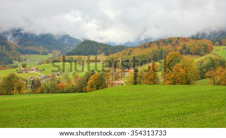 A small country village between green meadows and trees with farmhouse on a beautiful autumn hillside in Ramsau Bavaria Germany - stock photo