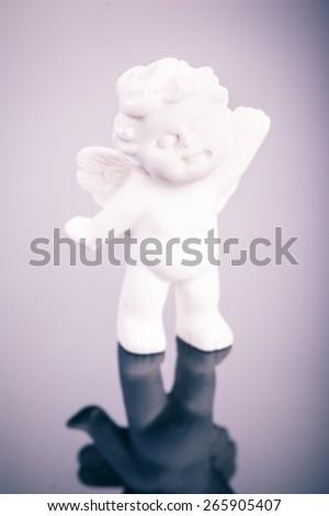 a small cute ceramic angel statuette over a dark surface - stock photo