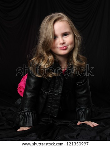 A Small Girl Puckers her Lips in a Silly Way with Mischievous Look - stock photo