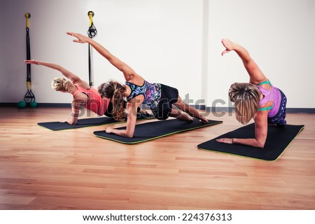 A small group of women are stretching in the gym - stock photo