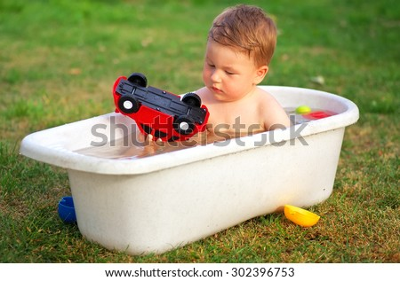A small happy baby bathed in the bath and playing with toys.  - stock photo