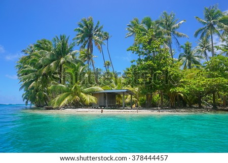 A small hut with tropical vegetation on the shore of an islet, Huahine island, Pacific ocean, French Polynesia - stock photo