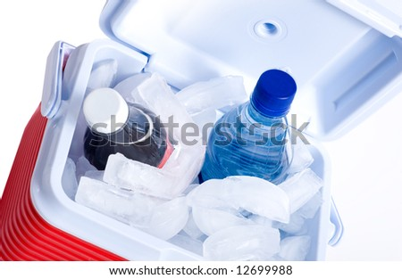 A small ice chest or cooler with drink including a cola and a bottle of water - stock photo
