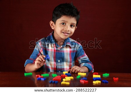 A small kid looks as he plays with toy alphabets in dark background - stock photo