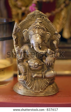 A small metal statue of the Hindu deity Ganesha sits on an altar - stock photo