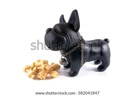 A small plastic toy dog with dog bones isolated on the white background - stock photo