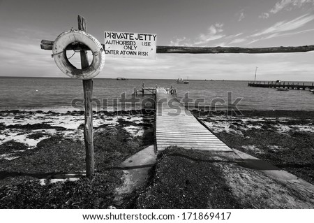 A small private jetty sticks out onto the water. In black and white. - stock photo