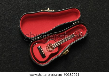 a small red guitar in its case - stock photo