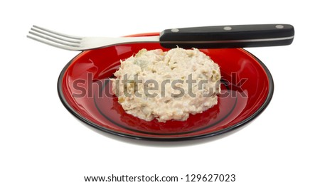 A small red plate with a small serving of tuna salad with fork on a white background. - stock photo