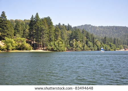 A small sailboat glides along the shoreline of Lake Gregory in Southern California. - stock photo