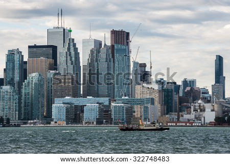 A small ship carries tourists from Algonquin Island to the Old Toronto skyscrapers, Canada - stock photo