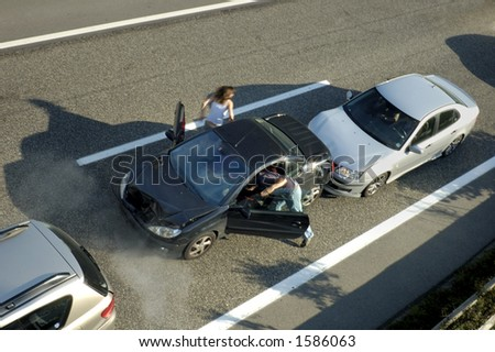 A small shunt on the freeway (motorway, autoroute, autobahn) a few seconds after it happened. Smoke is coming from under the bonnet of the black car. Motion blur on the passenger fleeing in panic. - stock photo