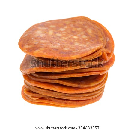 A small stack of pepperoni slices isolated on a white background. - stock photo