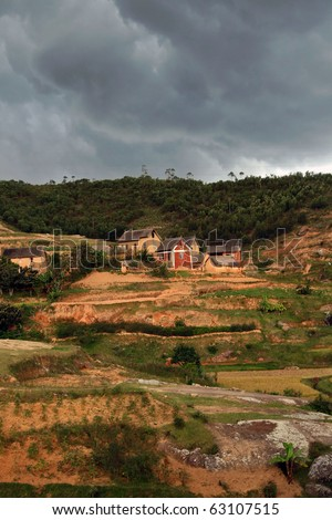 A small village in Madagascar just before a storm. Color of soil and houses is natural - not saturated. - stock photo