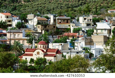 a small village with a church in the mountains of Crete, surrounded by vegetation - stock photo