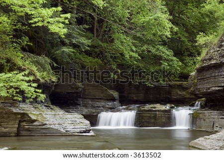 A small waterfall along Enfield Glen in Robert Treman state park in New York. Green spring colors along the stream add to the beauty of the scene. - stock photo